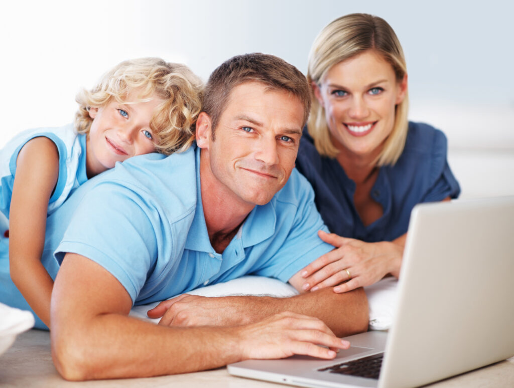 Portrait of smiling middle aged man using laptop with beautiful woman and son